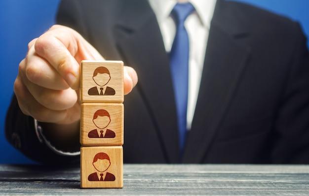 ビジネスリーダーは従業員と一緒にタワーブロックを構築します