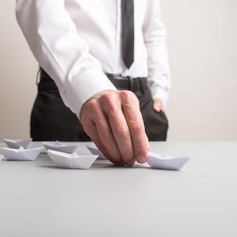 종이 접기 보트를 개념적 이미지로 만든 선두 배를 들고 있는 비즈니스 리더.