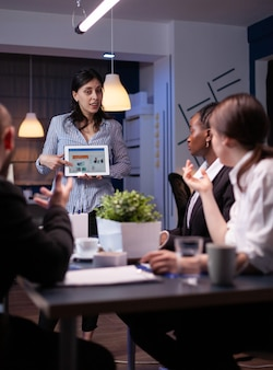 Business leader in meating room late at night discussing with her team holding tablet pc with charts. diverse multi-ethnic teamwork solving financial strategy. team working on deadline.