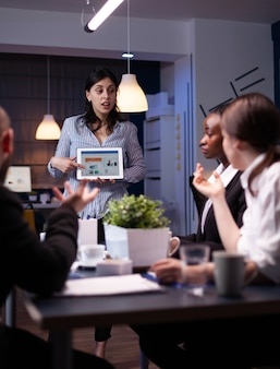 Business leader in meating room late at night discussing with her team