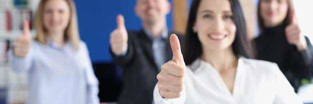 親指を立てる従業員のグループを持つビジネスリーダー