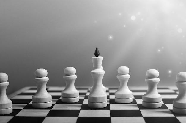비즈니스 리더십 개념. 흰색 체스 여왕은 폰과 함께 서서 승리로 이끈다. 흑백, 복사 공간, 하이라이트