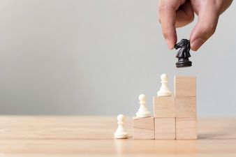 Business leadership concept with chess on top wood block ladder staircase