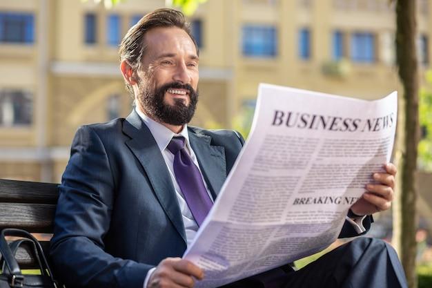 Деловая жизнь. веселый красивый бизнесмен сидит на скамейке и читает ежедневную газету
