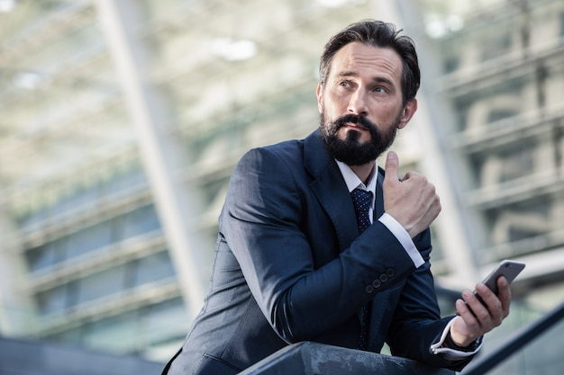 ビジネスライフ。思考に関与しながら彼の電話を使用して楽しいひげを生やしたビジネスマン