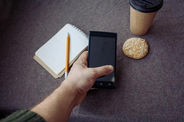 비즈니스, 라이프스타일, 음식, 사람, 그리고 커피 개념 - 갈색 패브릭 배경에 연필, 노트북, 종이 커피 컵. 남자가 손에 전화를 들고 있다