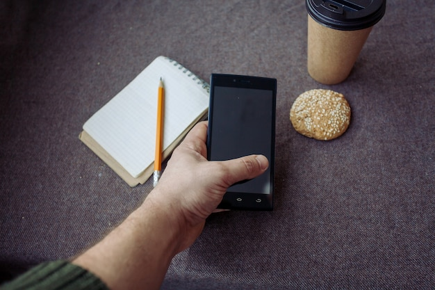 Business, lifestyle, food, people, and coffee concept - pencil, notebook and paper coffee cup on a brown fabric background. man is holding a phone in his hand