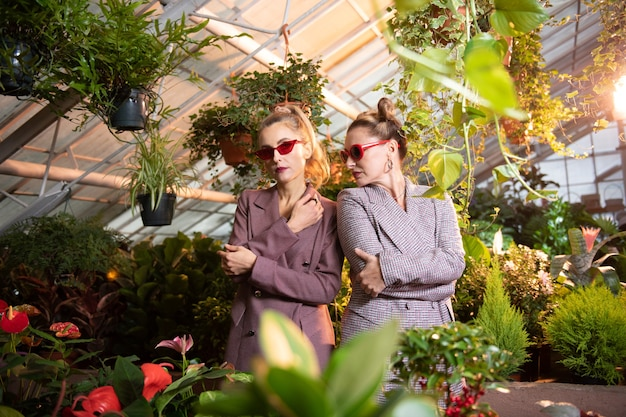 Business look. confident serious women standing together cross handed while being in the greenhouse