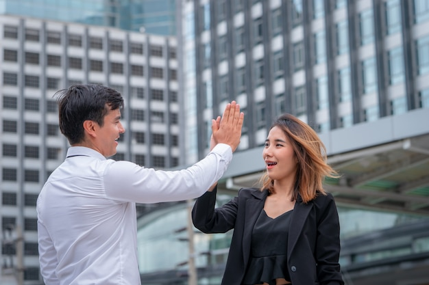 Business lover couple is hi five for success in modern city