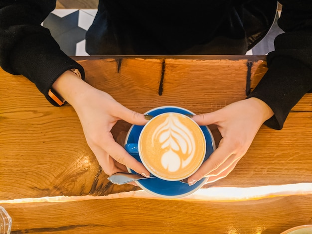 여성용 비즈니스 점심 에스프레소 머그는 빈티지 나무 탁자에 있는 파란색 컵에 카푸치노를 손에 넣습니다.