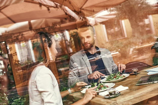 Business lunch man and woman sitting at table at restaurant eating healthy fresh salad discussing