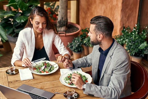 Business lunch man and woman sitting at table at restaurant eating healthy fresh salad talking