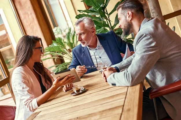 Business lunch three people in the restaurant sitting at table discussing project woman holding