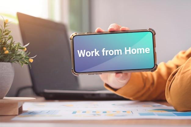 ビジネス男性のカジュアルウェアスマートフォンの画面にメッセージを表示在宅勤務を表示します。