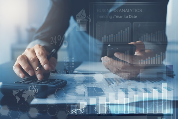 Business man analysing market report with business analytics dashboard on virtual screen