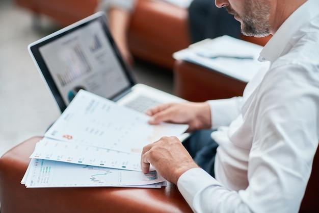 ビジネス文書と財務スケジュールを分析するビジネスマン