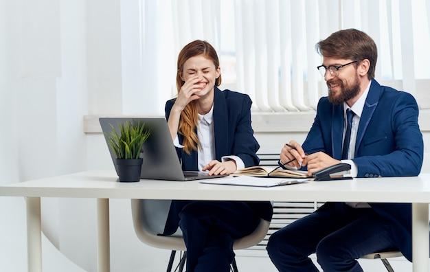 仕事でスーツを着たビジネスマンときれいな女性が開いたラップトップとポットに花を持ってオフィスで。