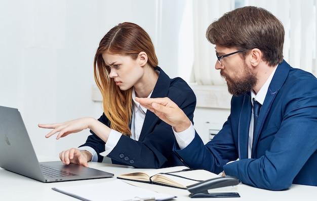 仕事でスーツを着たビジネスマンときれいな女性が開いているラップトップとポットに花とオフィスで