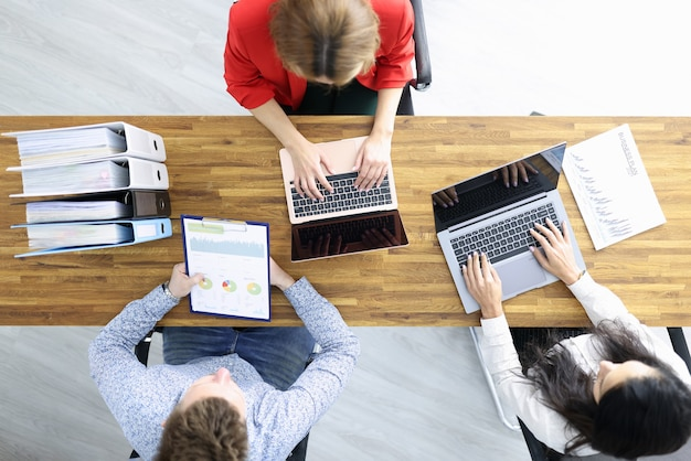 비즈니스 남자와 두 여자는 사무실에서 노트북과 문서와 나무 테이블에 앉아있다. 협상 개념의 조직.