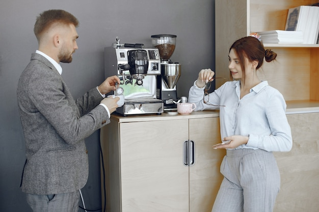 Деловой мужчина и женщина в офисе. перерыв на кофе в коридоре большой корпорации.