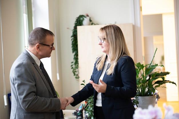 Деловой мужчина и женщина, давая рукопожатие в офисе