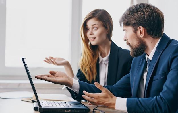 ノートパソコンのオフィスワークの同僚の専門家の前でビジネスの男性と女性。