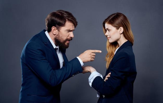 Деловой мужчина и женщина в костюме, жестикулирующие руками на сером пространстве.