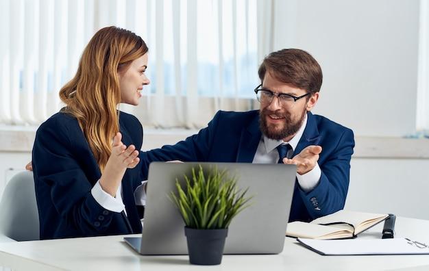 ラップトップと花鉢植えのオフィススタッフのコミュニケーションとスーツを着たビジネスの男性と女性。