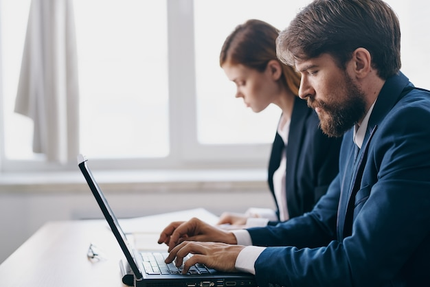 ラップトップのキャリアネットワーク技術の前にオフィスでビジネスの男性と女性。高品質の写真