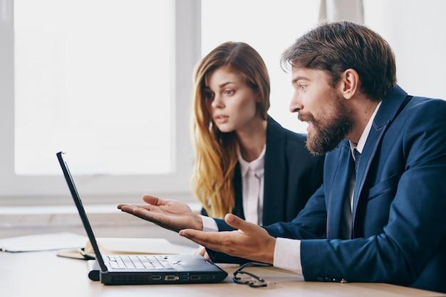 ノートパソコンのキャリアの仕事の専門家の前でオフィスでビジネスの男性と女性