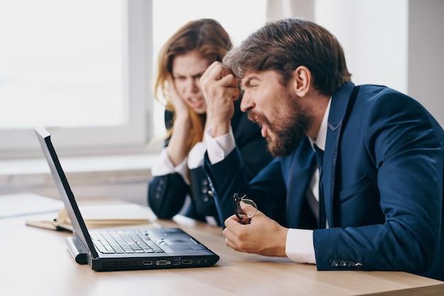 Деловой мужчина и женщина в офисе перед профессиональными профессионалами работы ноутбука