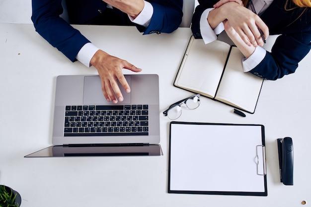 ビジネスの男性と女性のラップトップとテーブル上のドキュメント