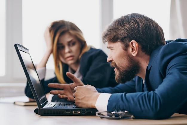 Деловой мужчина и женщина, сидя за столом с чиновниками связи ноутбука