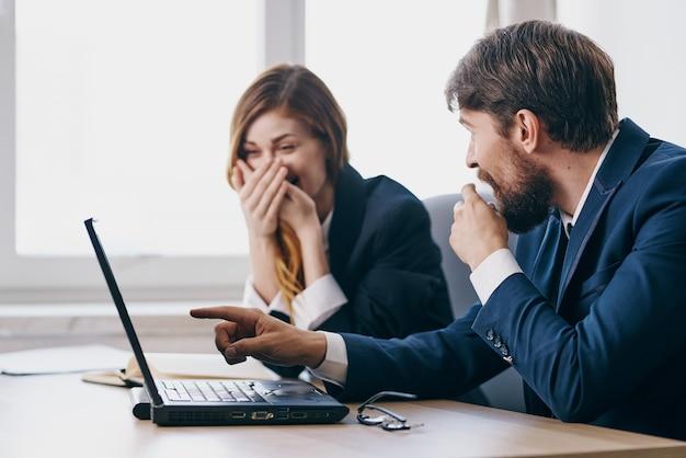 Деловой мужчина и женщина, сидящие за столом с профессионалами в области коммуникации ноутбуком