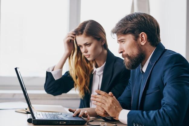 Деловой мужчина и женщина, сидя за столом с портативными коммуникационными технологиями. фото высокого качества