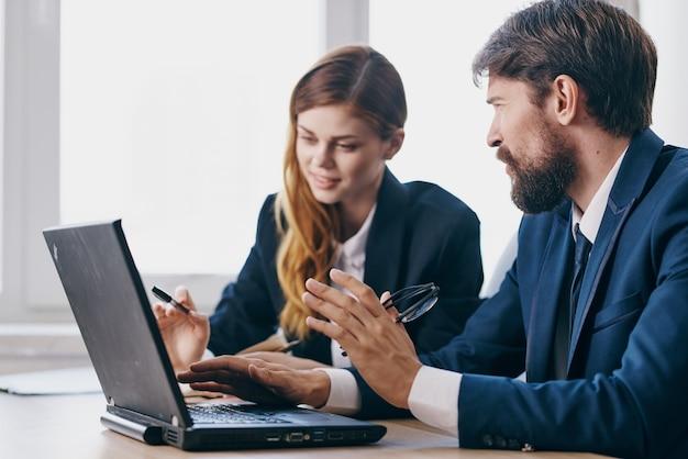 노트북 통신 기술을 사용하여 책상에 앉아 있는 사업가와 여성