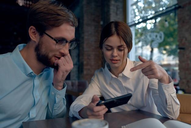 비즈니스 남자와 여자 카페에서 테이블에 앉아 전화를보고