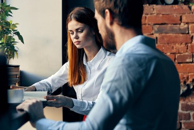 テーブルワークコミュニケーションオフィスに座っているビジネスの男性と女性