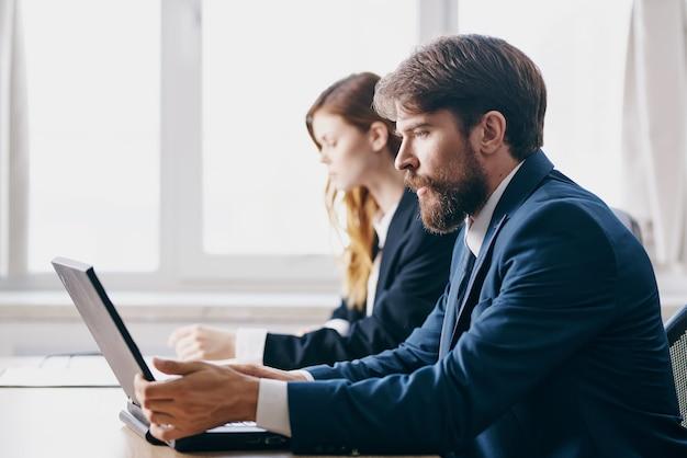 ノートパソコンのチームワークのインターネット関係者の前に座っているビジネスの男性と女性