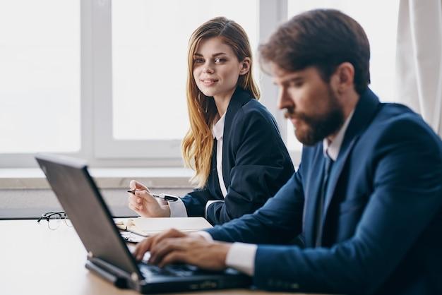 Деловой мужчина и женщина, сидящие перед ноутбуком в команде интернет-чиновников
