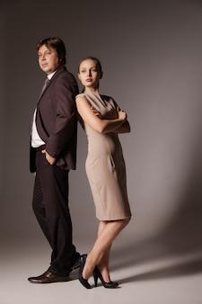 Деловой мужчина и женщина, стоящие спиной к спине, изолированные на коричневом фоне. концепция совместной работы