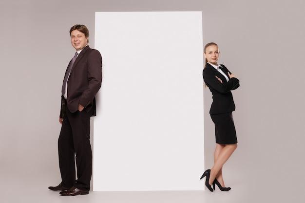 Деловой мужчина и женщина, стоящие спиной к спине по обе стороны от пустого баннера, изолированного на сером фоне. концепция совместной работы