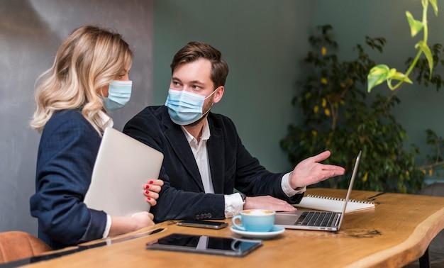 医療用マスクを着用しながら新しいプロジェクトについて話しているビジネスの男性と女性