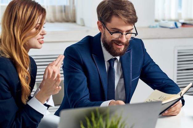 ラップトップオフィス技術の前のテーブルで話しているビジネスの男性と女性。高品質の写真