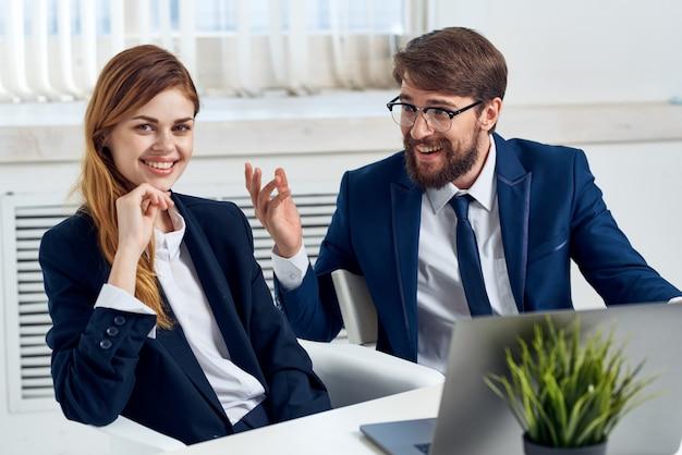 ノートパソコンチームテクノロジーの前でテーブルで話しているビジネスの男性と女性