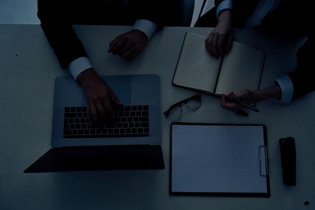 ラップトップ技術を使用してオフィスでビジネスの男性と女性のチームワーク