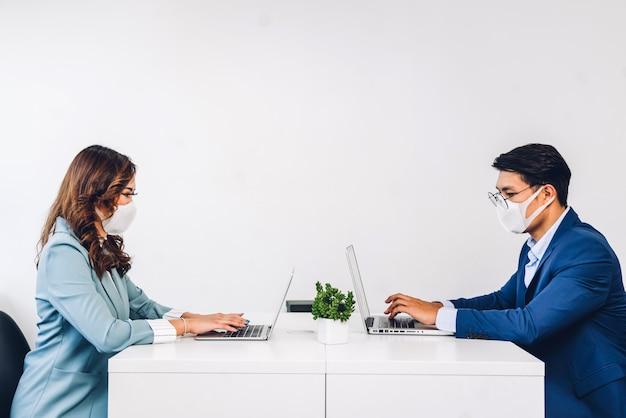 ラップトップコンピューターの作業と計画会議保護マスクを使用してビジネスの男性と女性