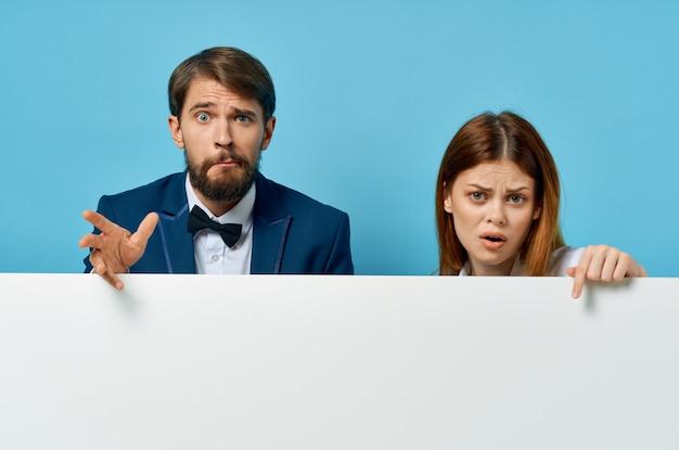 白いモックアップポスター広告サインコピースペーススタジオを持つビジネスの男性と女性