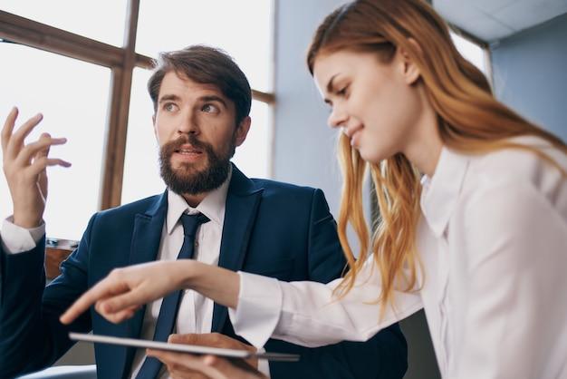 Деловой мужчина и женщина работают с совместной работой должностных лиц планшета. фото высокого качества