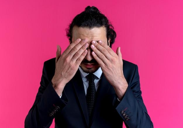 Uomo d'affari in abito nero e occhiali che coprono gli occhi con le mani in piedi sul muro rosa
